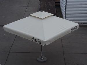 Cream metal parasol umbrella with Coca Cola branding printed on the sides